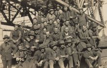 A group photograph of workers sitting under a large steel construction. Several smoke pipes and most wear overalls and hats.