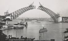 A photo of cranes of on each side of the arch of the Sydney Harbour Bridge before the sides converged in the centre.