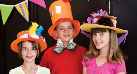 Three children wearing handmade cardboard hats.