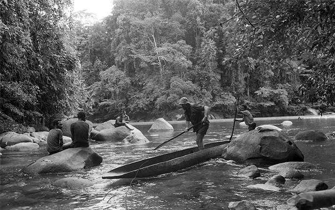 Black and white photo on men in canoe with others seated on rocks in Purari River