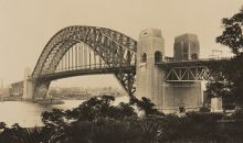 A black and white photograph of the Sydney Harbour Bridge, with a steam ferry passing under it.