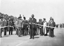 Black and white photo of dignitaries, with one man standing forward to cut a ribbon.