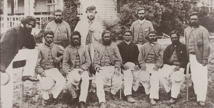 Black and white reproduction photograph of a cricket team of eleven men, six of whom are seated. They are outside in front of a building.