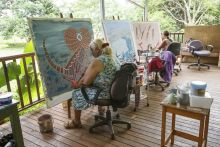 Two women working on Aboriginal paintings.