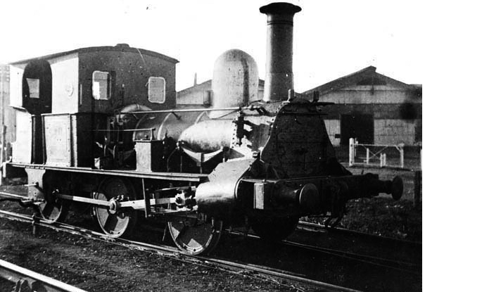 Slightly scratched photo of an early steam engine with railway sheds in the background.