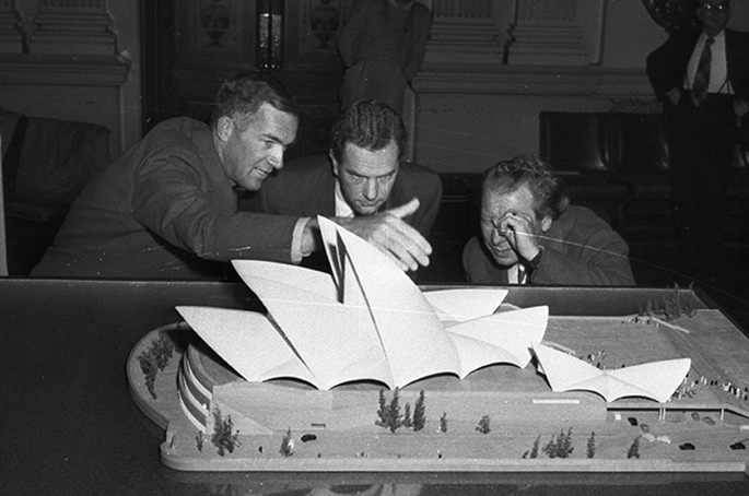 Utzon and two other men scrutinising a model of the Opera House.