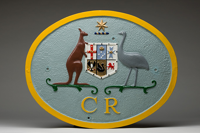Oval plate with Australian coat of arms with the letters CR underneath.