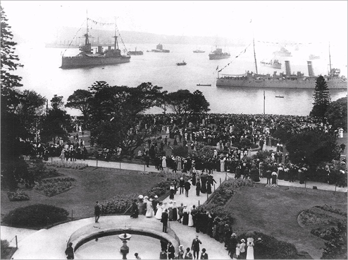 Two of that fleet unit's warships and several smaller ones in background, with hundreds of people looking on from a park, possibly the Botanic Gardens.