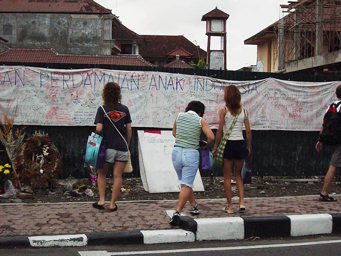 Three young women with their backs to the camera look at a memorial consisting of a long white sheet covered in handwriting, pinned to a fence above some wreaths and flowers.