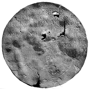 A battered disc, much worn and with holes in it. Words are visible, neatly inscribed in capitals in the top two thirds of the plate.