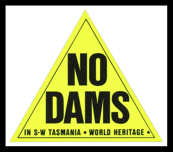 Yellow triangle on black background. Within the triangle are the words NO DAMS in capital letters. Beneath these are the words 'IN S W TASMANIA. WORLD HERITAGE.
