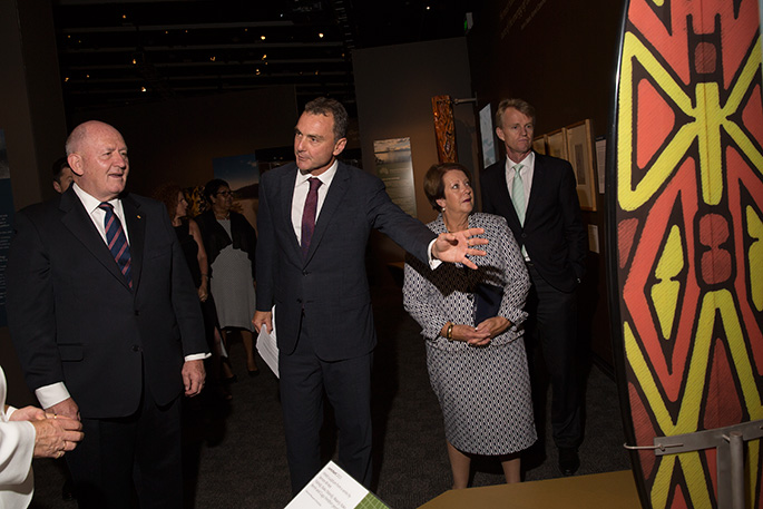Three men and a woman in an exhibition look at shield painted with red and yellow geometric symbols.
