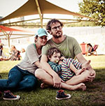 Man, woman and child sitting on grass