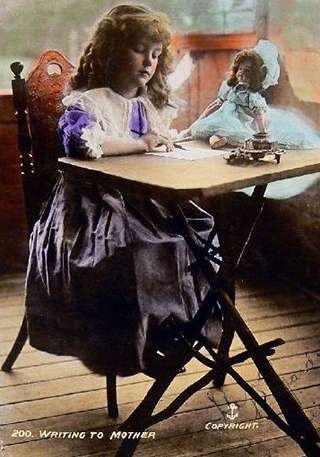 A postcard featuring a coloured photograph of a girl seated at a table with a doll on the table, and a message on the back. The text on the front reads '200. WRITING TO MOTHER'.