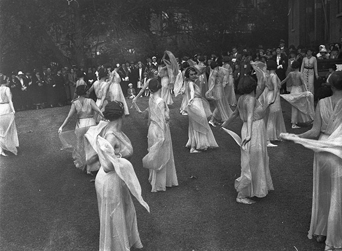 Photo taken from the rear of the stage with audience in the background. The 20 or so dancers are all wearing flowing white dresses