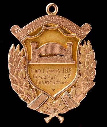 Faded gold-coloured metal badge with an image of the bridge and the words 'From L Ennis OBE, Director of Construction'.
