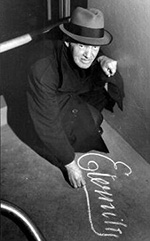 Black and white photo of a man drawing on the pavement with chalk