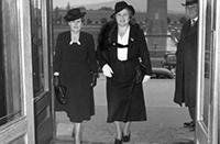 Two women walking through a doorway