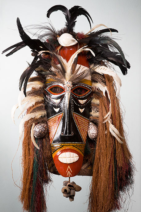 Cultural mask with black and ochre tones, feathers, and other materials. - click to view larger image