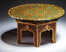 Varnished table with geometric and arabesque decoration. Made from wood and metal.