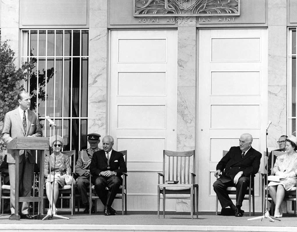 Prince Phillip speaking at a lectern with Holt and Menzies seated. Other dignitaries and their wives are also present. Behind them is the main door of the Mint.