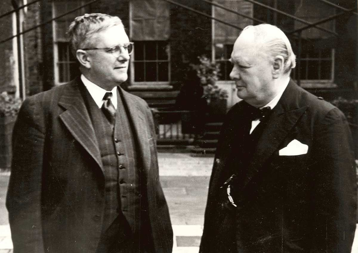 Evatt and Churchill stand next to each other looking at each other.