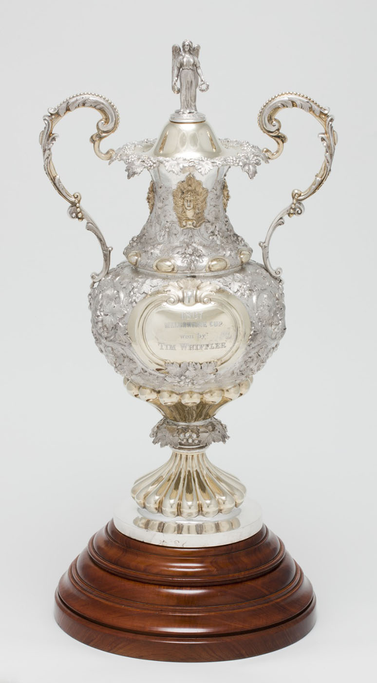 Carved silver trophy with gold inlay and two onate handles mounted on a wooden base. - click to view larger image