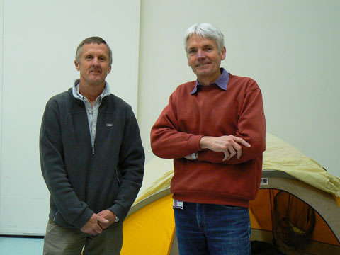 Geoff Bartram and Matthew Higgins stand in front of a yellow tent. - click to view larger image