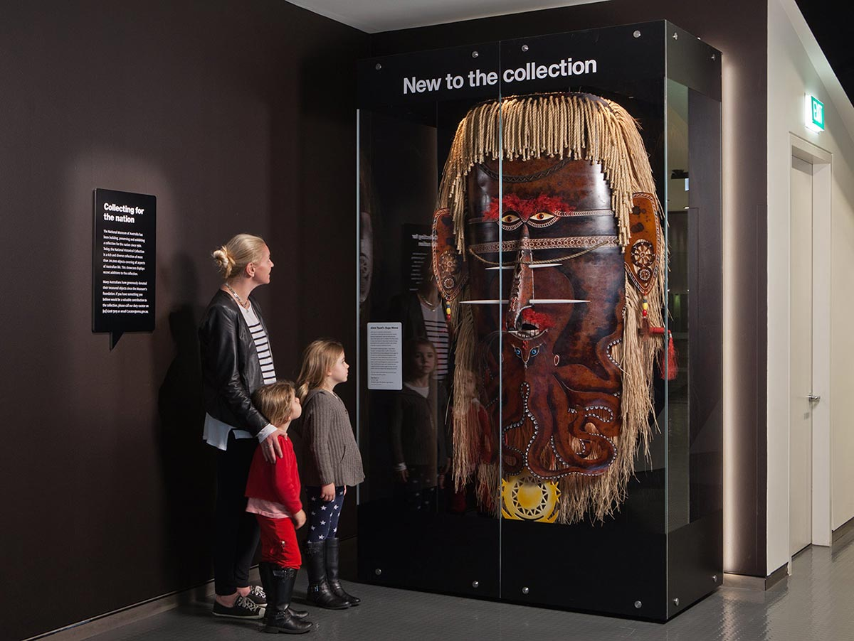 A woman and two small girls stand to the left, looking at a large mask on display in a perspex case under the heading 'New to the collection'.
