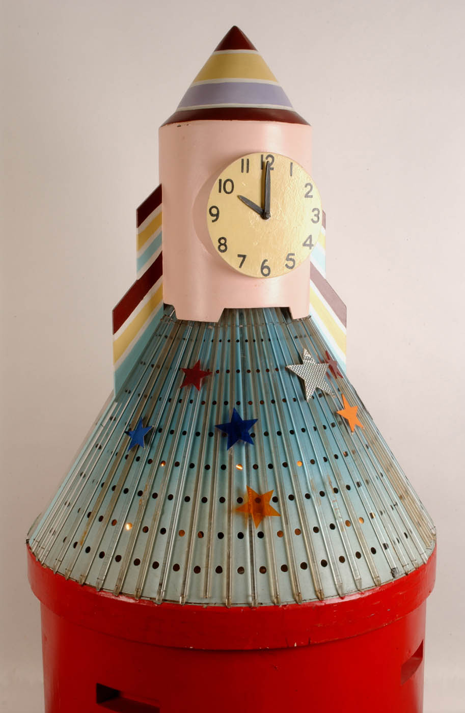 A large clock in the shape of a rocket with a red cylindrical wooden base with a light blue perforated metal skirt covered in vertical plastic rods, a light pink wooden trunk and painted striped cone top. - click to view larger image