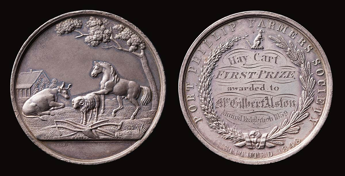 Photo showing two circular medal faces, side by side. The face on the left shows an image of a cow, sheep and horse in a rural scene. The right is inscribed 'Hay Cart/First Prize/awarded to/Mr Gilbert Alston/Annual Exhibition 1859'.  - click to view larger image