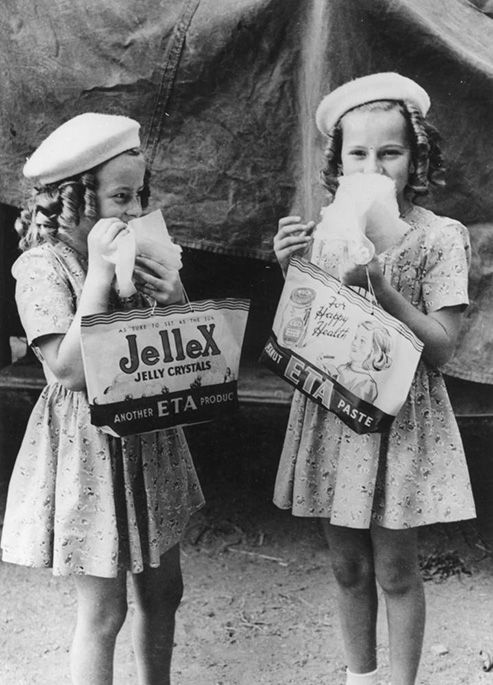 Two young girls eat a treat while holding show bags. One reads 'Jellex Jelly Crystals'; the other 'Peanut ETA Paste'. - click to view larger image