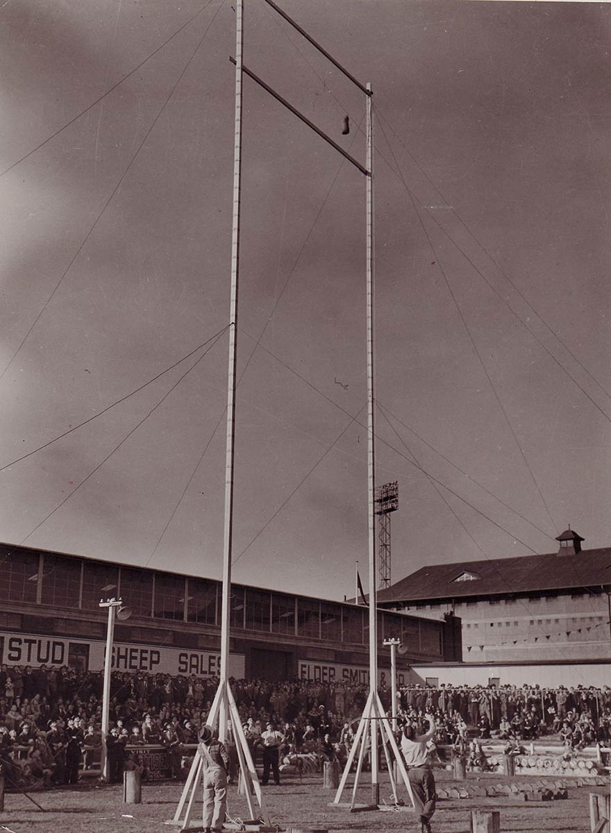 Black and white photograph showing a crowd of people looking skyward at a small wheatbag which has been flung high into the air, between two vertical poles. - click to view larger image