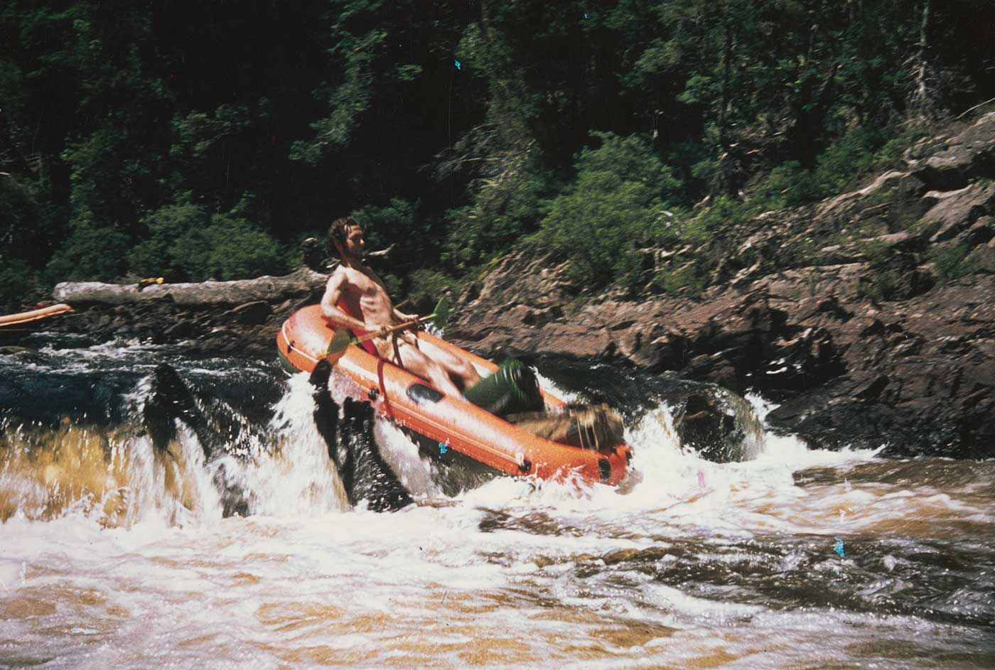 A man in a raft leans back as he negotiates the rapids in a river. - click to view larger image