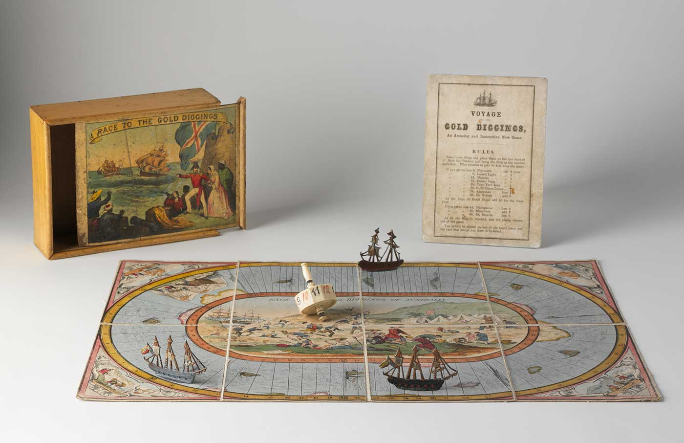 A playing board with three sailing ship markers and a dice, in front of a box with 'RACE TO THE GOLD DIGGINGS' printed on the sliding lid, and a printed rule sheet. - click to view larger image