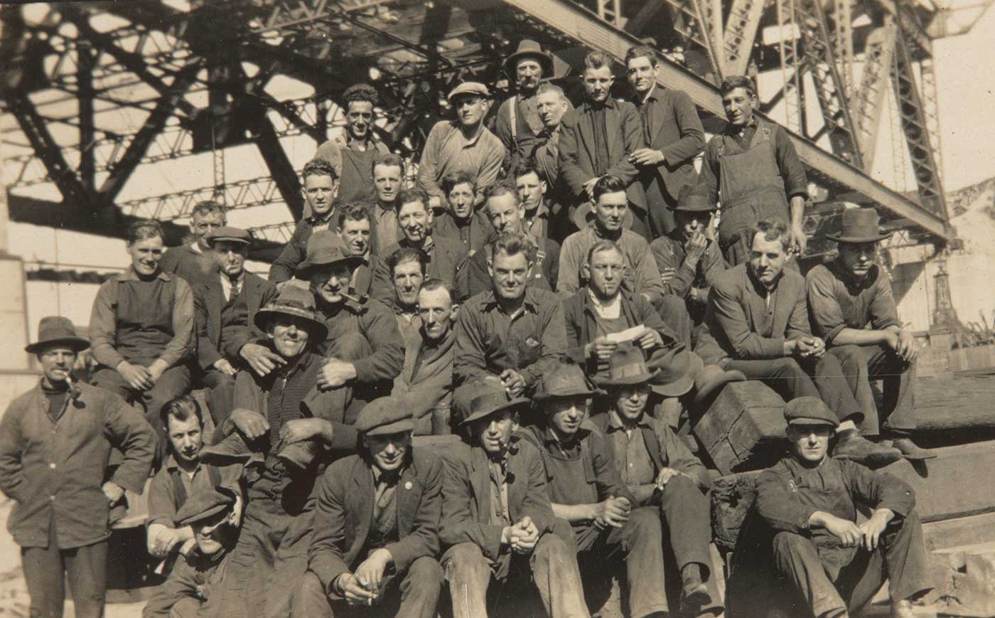 A group photograph of workers sitting under a large steel construction. Several smoke pipes and most wear overalls and hats. - click to view larger image