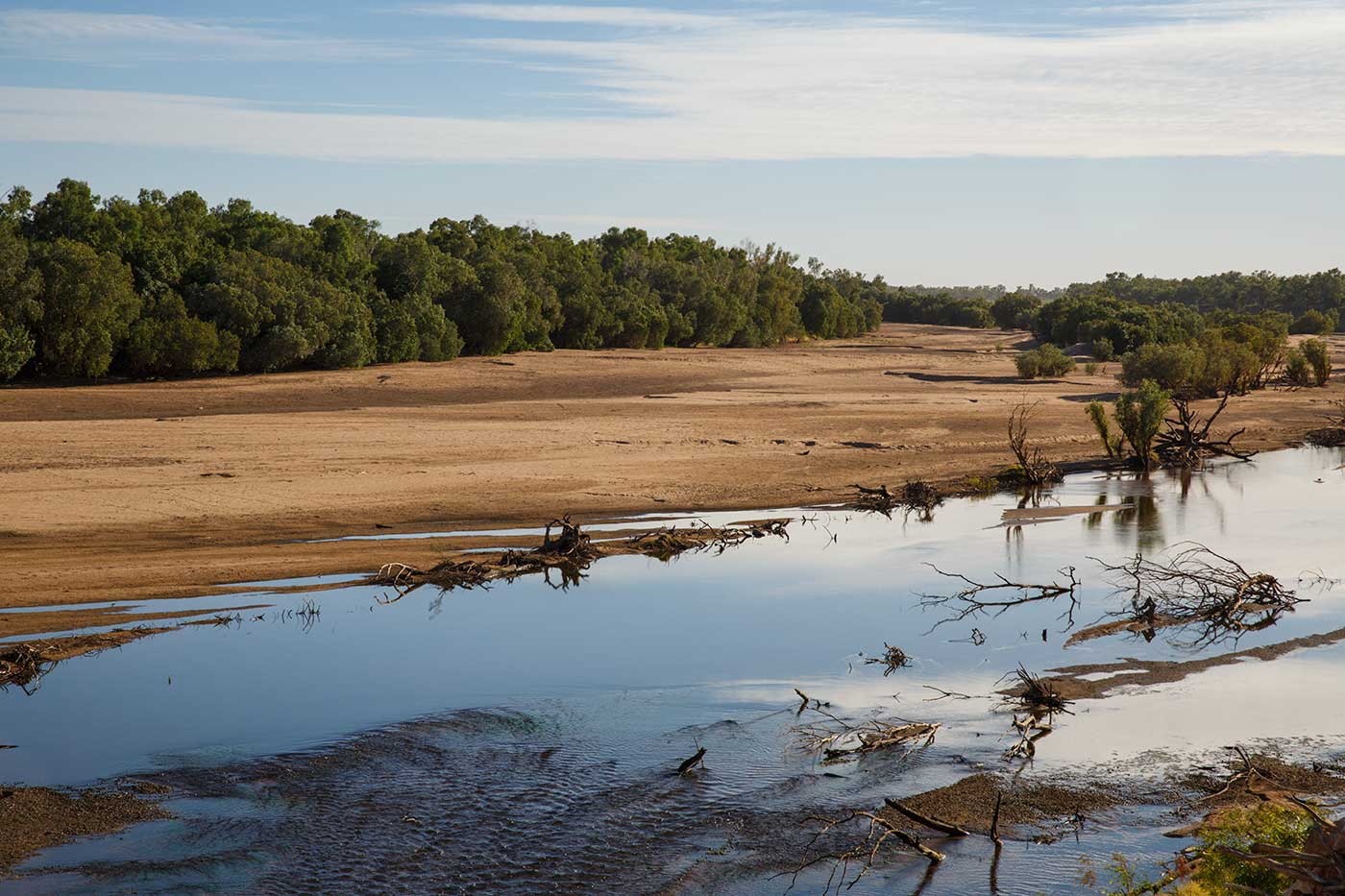 Colour photograph of a small, low river with sandy flats extending to a tree-lined bank. - click to view larger image