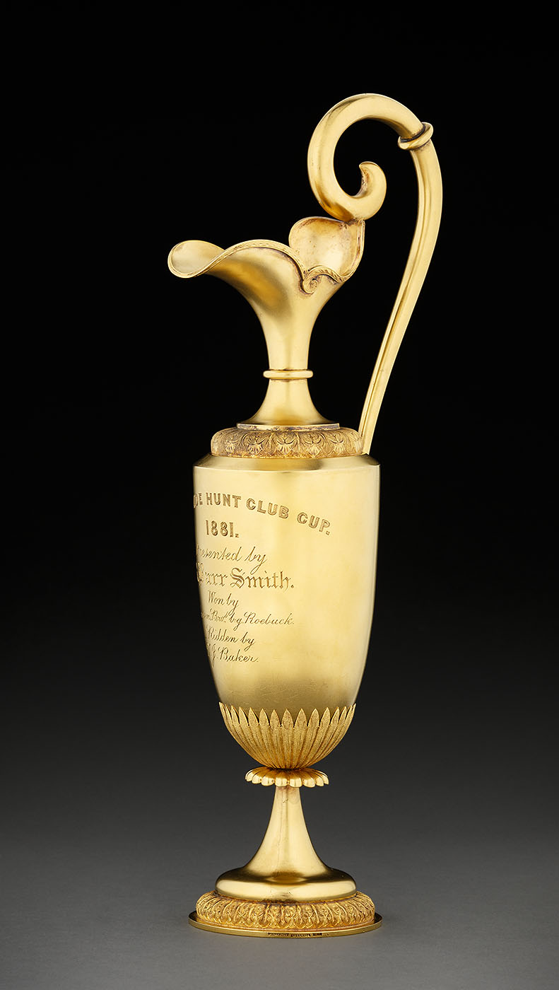 Gold trophy with scroll handle and ornate base. - click to view larger image