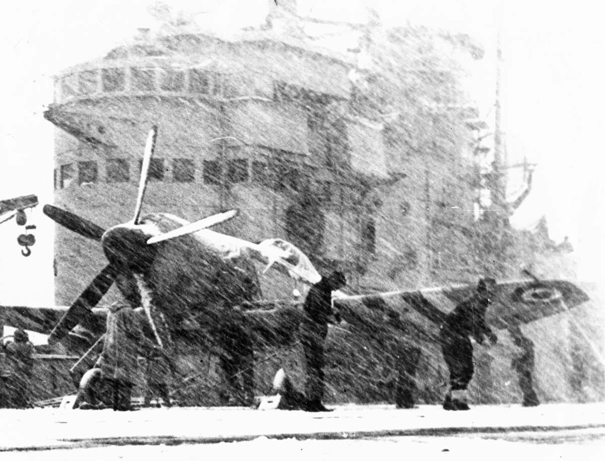 A fighter plane on the snow-covered deck of an aircraft carrier attended to by crew, with snow blowing hard.