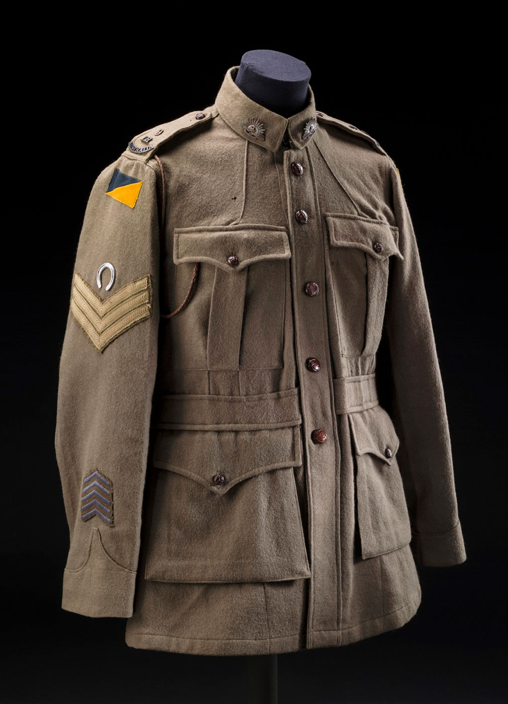 Khaki jacket with buttons down the front, four front pockets, and various patches on the sleeve.  - click to view larger image