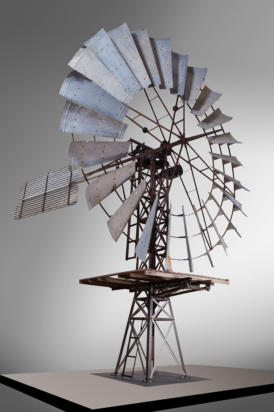 A photo of the top section of a windmill on display indoors