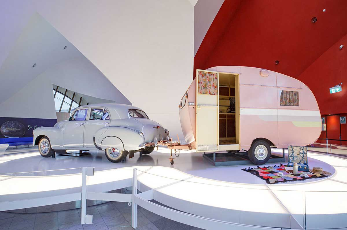 Display featuring a vintage car attached to a vintage pink caravan. A picnic set is laid out on a blanket in front of the caravan.