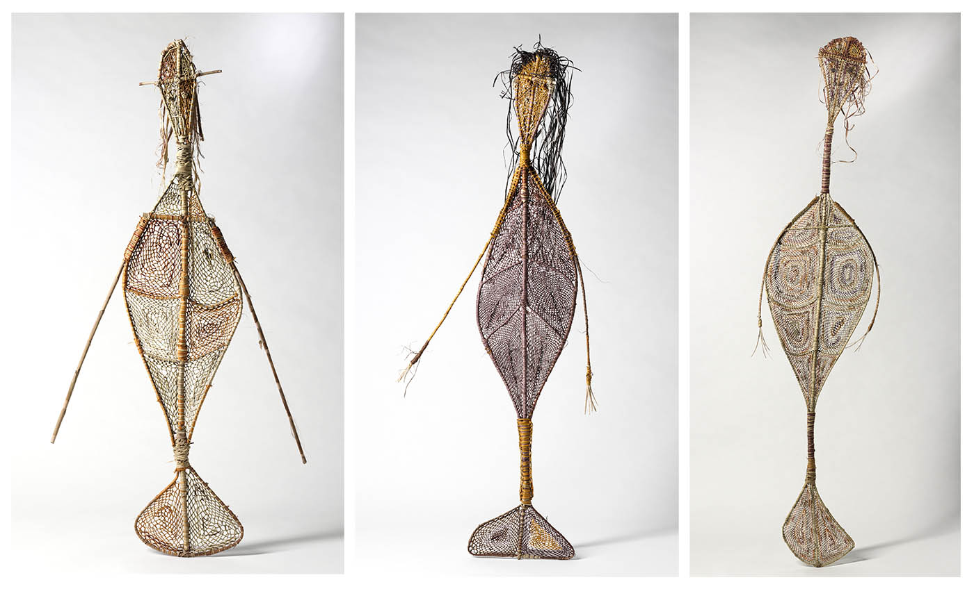 Three woven grass, mermaid-like yawkyawk sculptures with arms, tails and trailing hair