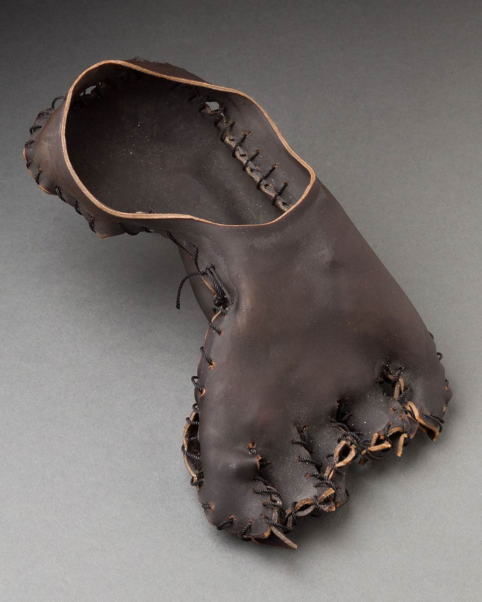 A sculpture made from lengths of dark brown, bull sea kelp sewn together with black nylon string forming the shape of a left foot. - click to view larger image