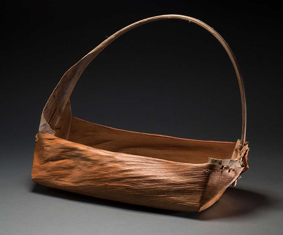 A rectangular shaped basket with a handle made of natural fibres. The handle has other natural fibres beige in colour wound around it.