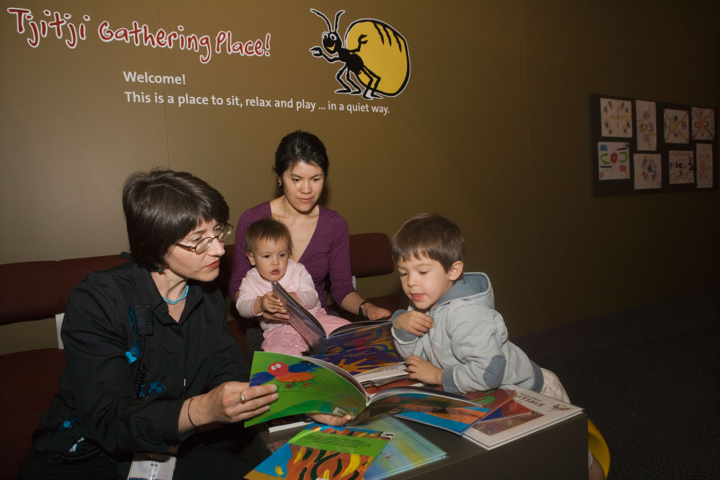 Museum host reads a book to a female visitor and two young children in the Tjitji Gathering Place. - click to view larger image