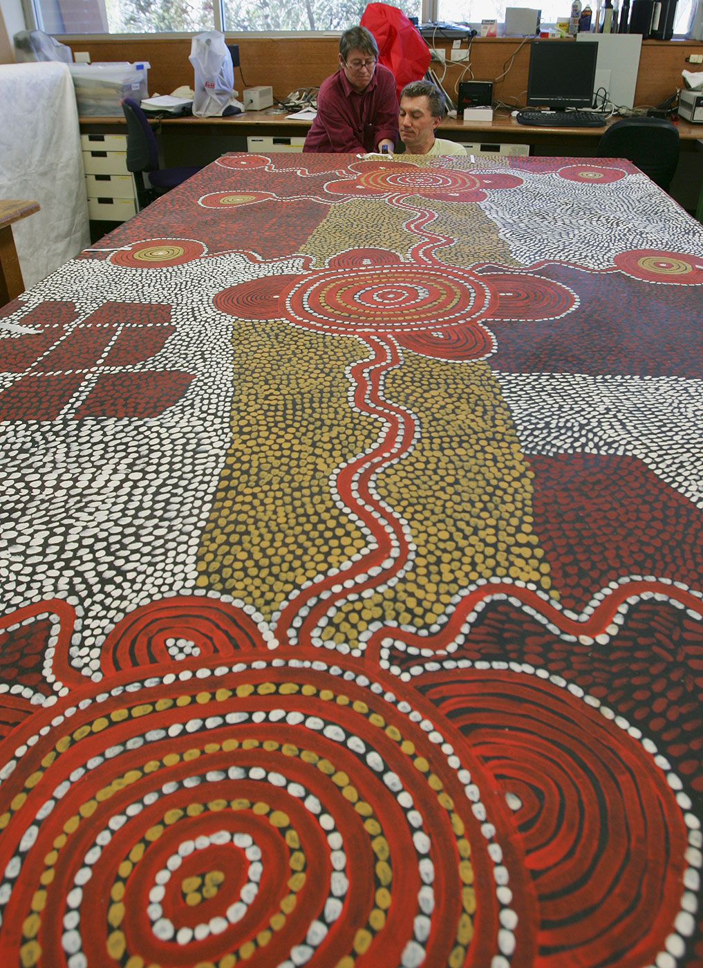 Two conservators inspect far end of large Yumari 1976 dot painting by Uta Uta Tjangala. - click to view larger image