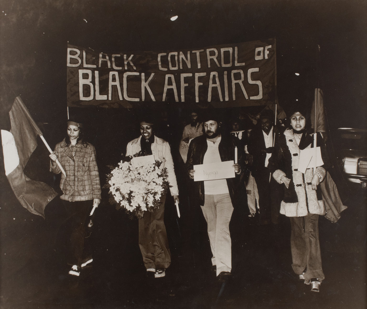 Black and white photograph showing three women and a man walking under a banner which reads 'BLACK CONTROL OF BLACK AFFAIRS'. The woman on the left carries an Aboriginal flag, the next woman along carries a large bunch of white flowers and a man to her right carries a small sign. More people are partially visible in the background.