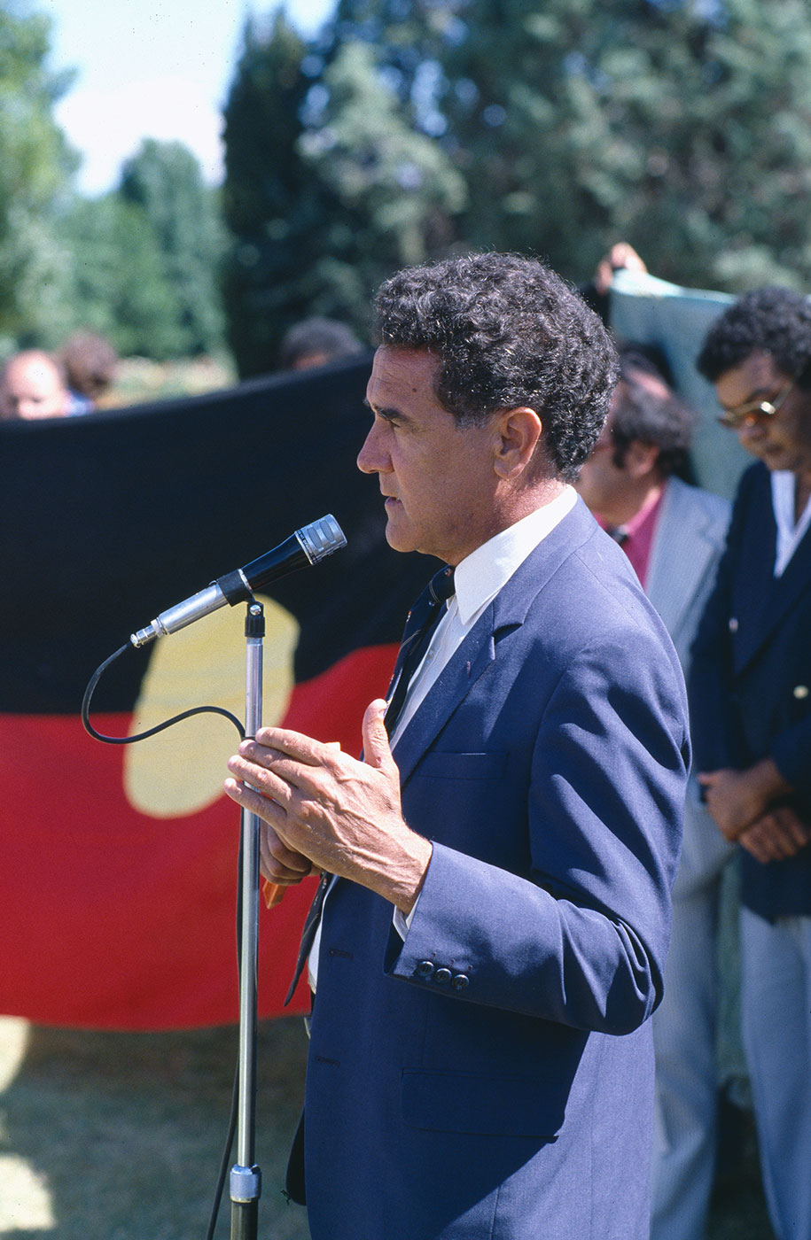Colour photograph showing Charles Perkins in side profile. He wears a dark blue jacket, white shirt and black tie and stands speaking at a microphone. An Aboriginal flag is partially visible in the background. - click to view larger image