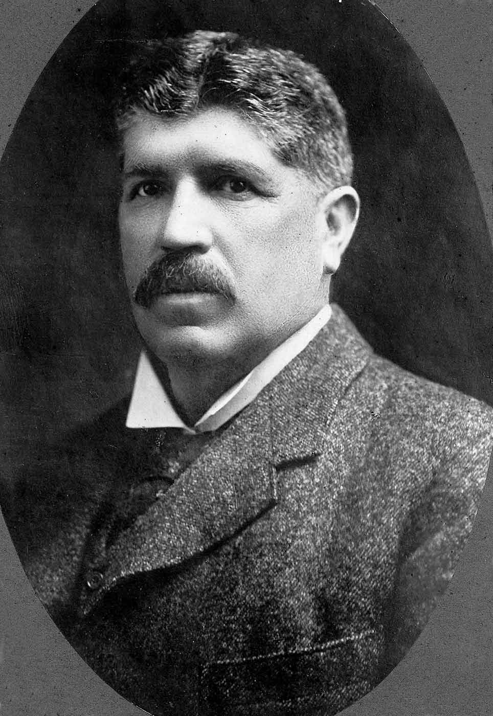 Black and white portrait of a man with a moustache and wearing a wool suit jacket and tie. - click to view larger image